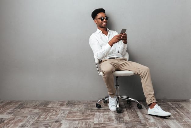 Homem sentado em uma cadeira e segurando o telefone móvel Foto gratuita