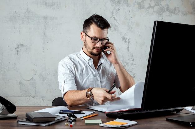 Homem sentado em uma mesa no escritório, falando ao telefone, decide uma questão importante. o conceito de trabalho de escritório, uma startup. copie o espaço. Foto Premium