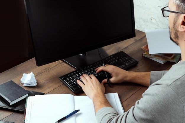 Homem sentado em uma mesa no escritório Foto Premium