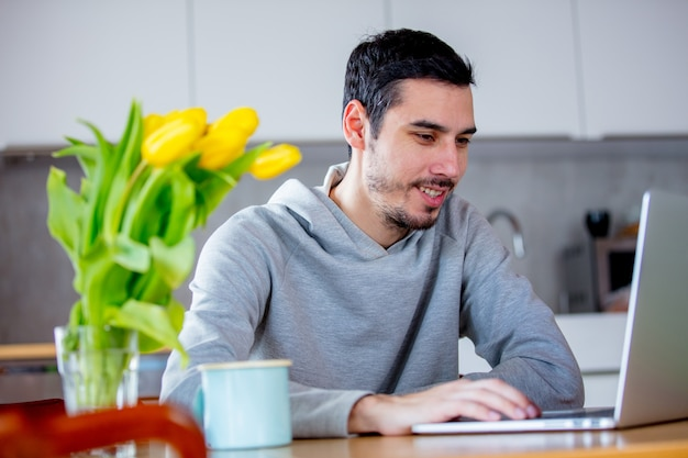 Homem sentado na mesa com café e laptop Foto Premium