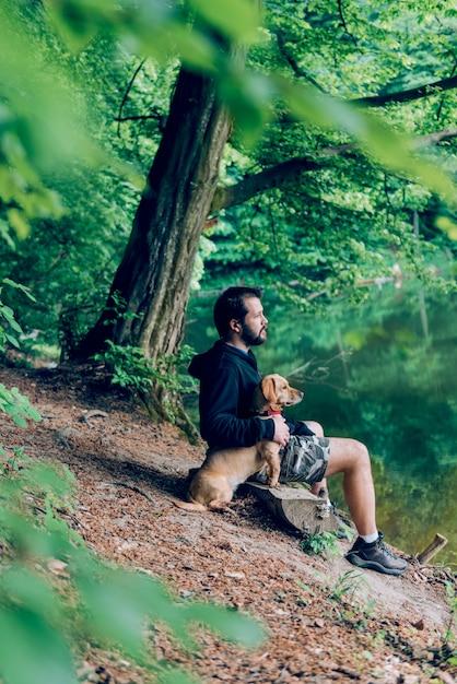 Homem sentado no banco com o cachorro à beira do lago Foto Premium