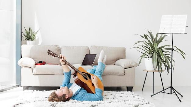 Homem sentado no chão e tocando guitarra vista longa Foto Premium