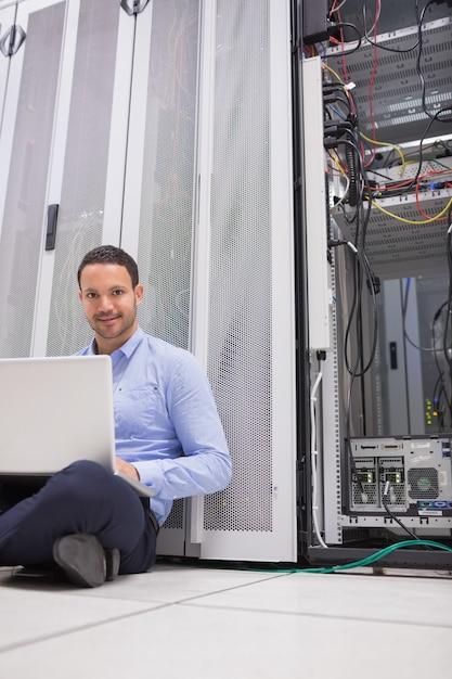 Homem sentado no chão usando laptop para verificar servidores Foto Premium