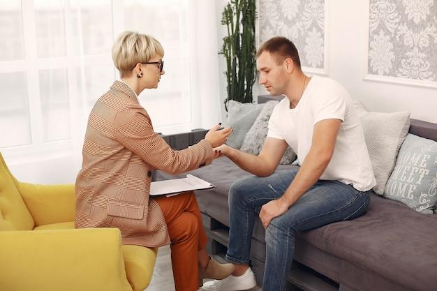 Homem sentado no consultório do psicólogo e falando sobre problemas Foto gratuita