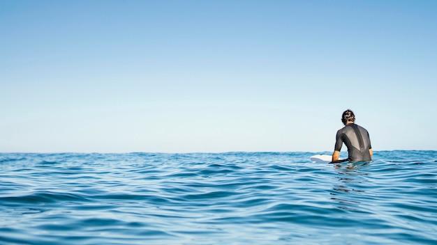 Homem sentado no espaço da cópia de água Foto gratuita