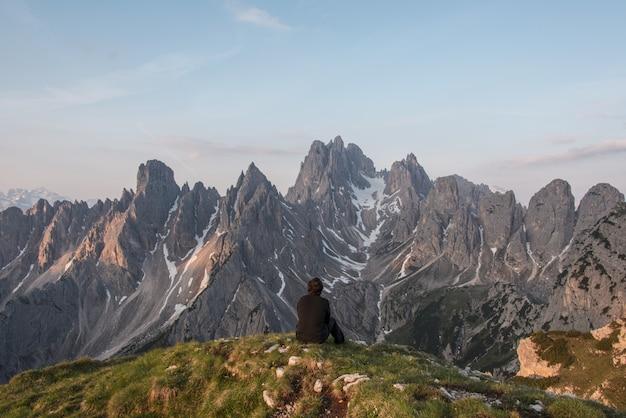 Homem sentado no penhasco de frente para a montanha cinza Foto gratuita