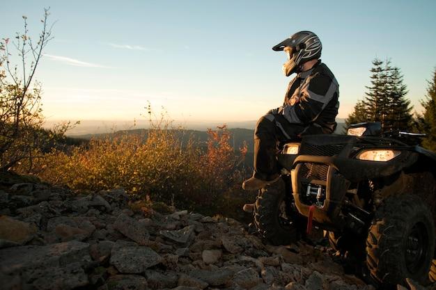 Homem sentado no pôr do sol de observação de veículos todo-o-terreno Foto Premium