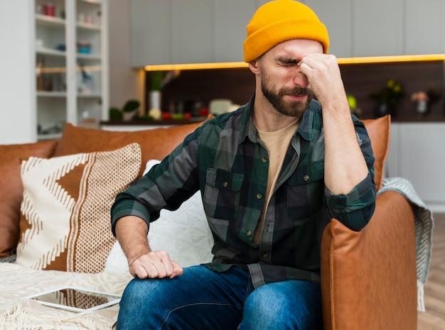 Homem sentado no sofá e com dor de cabeça Foto gratuita