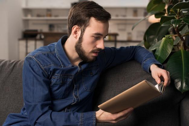 Homem sentado no sofá e lendo o livro Foto gratuita