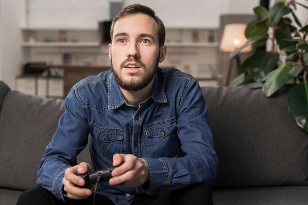 Homem sentado no sofá e segurando o controlador de jogo Foto gratuita