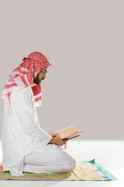 Homem sentado no tapete de oração Foto gratuita