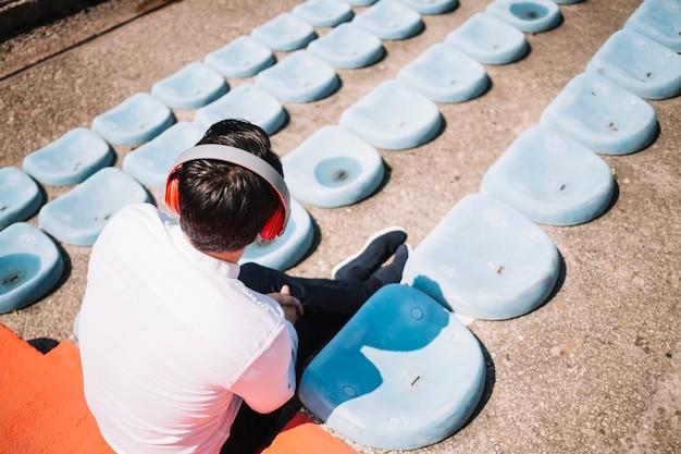 Homem sentado usando fones de ouvido Foto gratuita