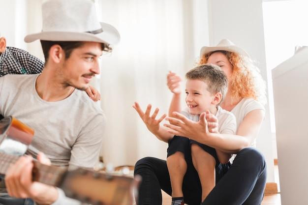 Homem, sentando, com, seu, família, violão jogo Foto gratuita