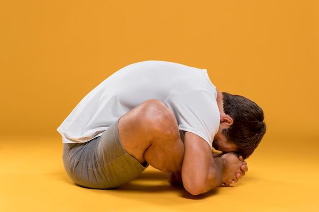Homem, sentando, frente, curvatura, ioga posa Foto gratuita