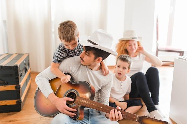 Homem, sentando, ligado, assoalho hardwood, com, seu, família, violão jogo Foto gratuita