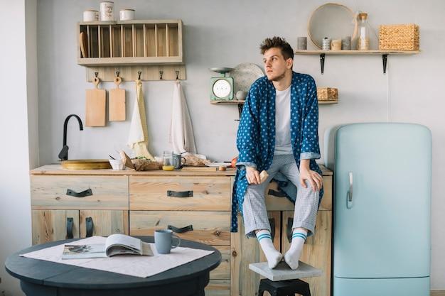 Homem, sentando, ligado, contador cozinha, segurando, alimento Foto gratuita