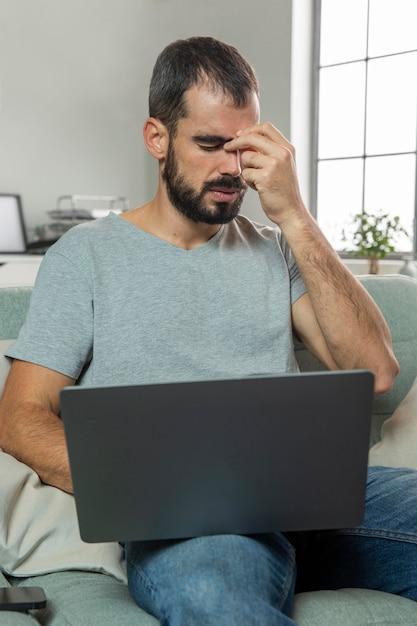 Homem sentindo dor nos olhos enquanto trabalha em um laptop de casa Foto gratuita