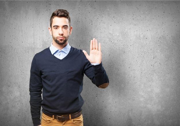 Homem sério com a palma da mão levantada Foto gratuita