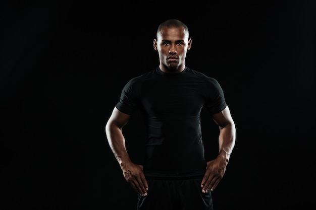 Homem sério de esportes afro-americanos com os braços nos quadris, olhando para a câmera Foto gratuita