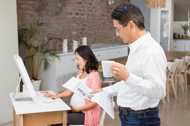 Homem sério, lendo jornal e tomando café em casa enquanto a mulher grávida está usando o laptop Foto Premium