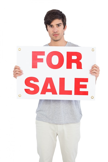 Homem sério, mostrando para a placa de venda Foto Premium