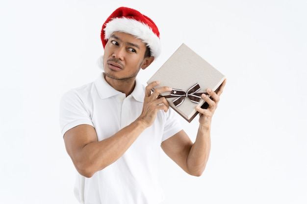 Homem sério, tentando adivinhar o que está dentro da caixa de presente de natal Foto gratuita