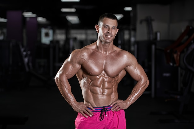 Homem sexy muscular bonito posando no ginásio. atleta bronzeada Foto Premium