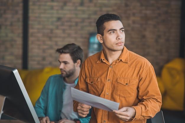 Homem simpático de cabelos escuros olhando para o lado enquanto fica de pé com um pedaço de papel Foto Premium