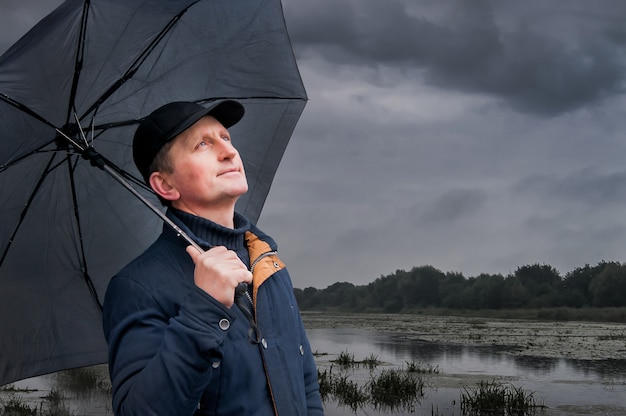 Homem sob o guarda-chuva, olhando para o céu Foto Premium