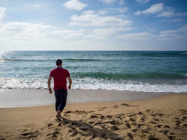 Homem solitário caminhando na praia sob um lindo céu nublado Foto gratuita