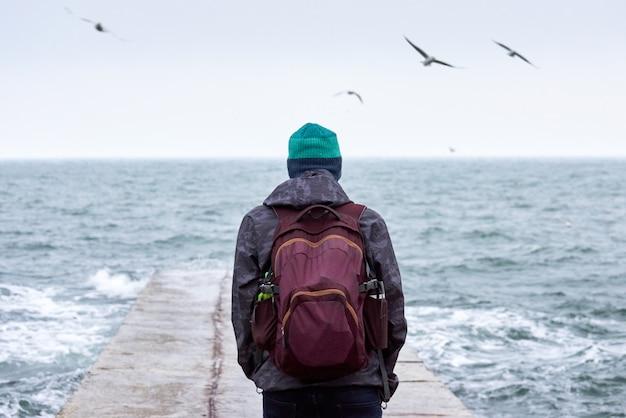 Homem solitário com mochila sentado no cais Foto Premium