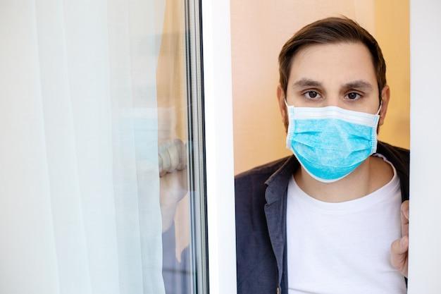 Homem solitário em quarentena com covid-19 em auto-isolamento em casa olha da janela. homem em quarentena de máscara médica protetora em casa. prevenção de pandemia de coronavírus. conceito de cuidados de saúde de medicina Foto Premium