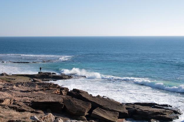Homem solitário olhando o mar Foto gratuita