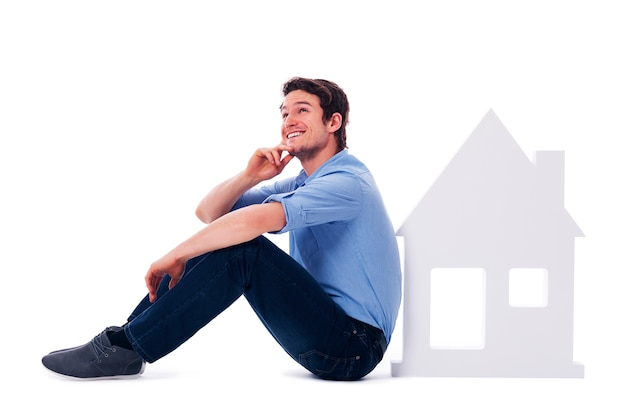 Homem sonhador sentado ao lado de uma placa para casa Foto gratuita