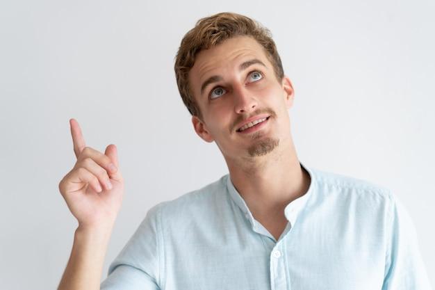 Homem sorridente apontando o dedo e olhando para cima Foto gratuita