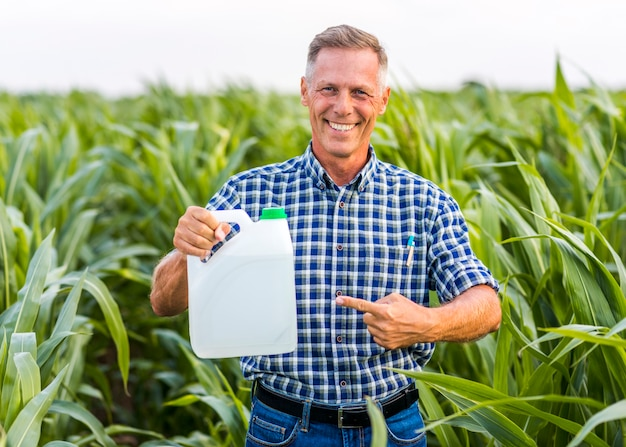Homem sorridente apontando para uma lata de inseticida Foto gratuita