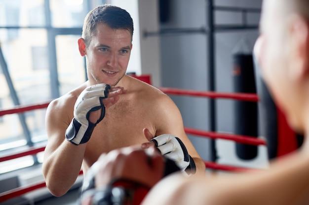 Homem sorridente, aproveitando a luta de boxe no ringue Foto gratuita
