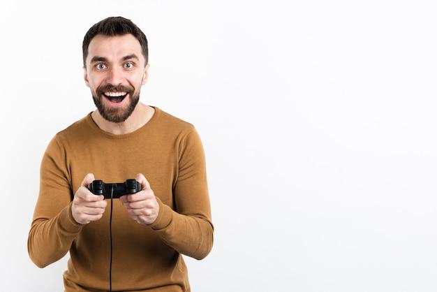Homem sorridente, brincando com o controlador de jogo Foto gratuita