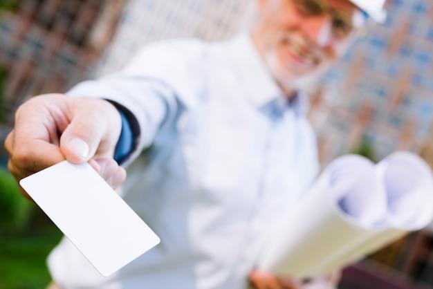 Homem sorridente com cartão mock-up Foto gratuita