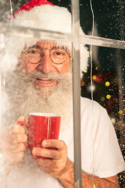Homem sorridente com chapéu de papai noel segurando uma caneca e olhando pela janela Foto gratuita
