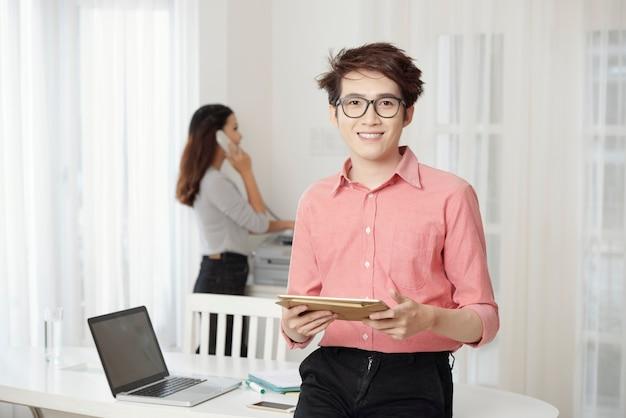 Homem sorridente com tablet no escritório Foto gratuita