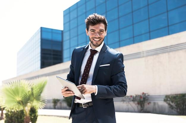 Homem sorridente com tablet, olhando para a câmera Foto gratuita