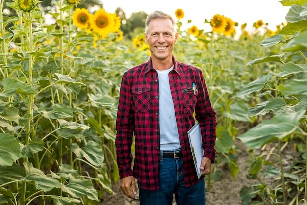 Homem sorridente com uma prancheta em um campo Foto gratuita