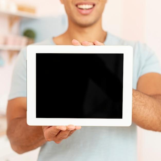 Homem sorridente de close-up, segurando o tablet Foto gratuita
