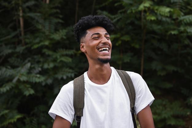 Homem sorridente de merda médio usando mochila Foto gratuita
