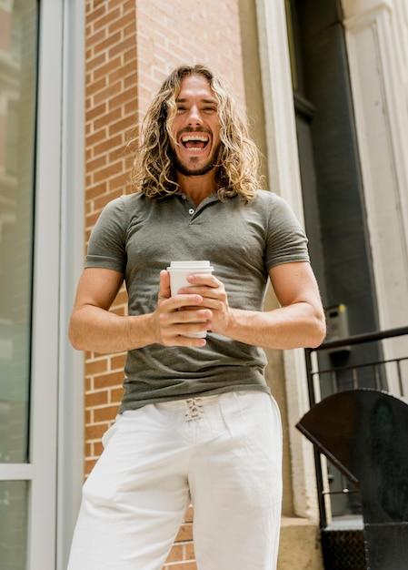 Homem sorridente, desfrutando de café ao ar livre Foto gratuita
