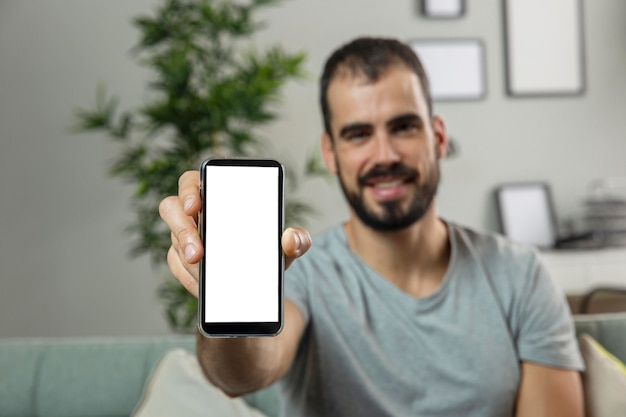 Homem sorridente em casa segurando smartphone Foto gratuita