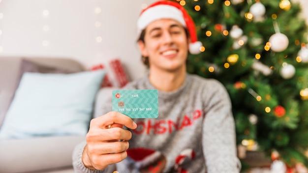 Homem sorridente, em, chapéu santa, segurando, cartão crédito Foto gratuita