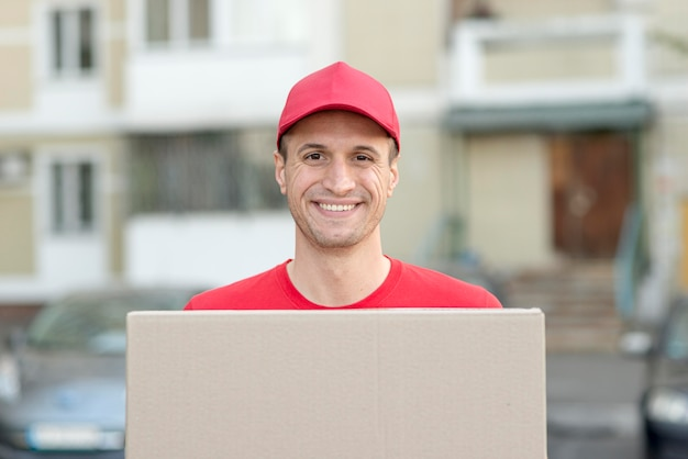 Homem sorridente, entregando o pacote Foto gratuita