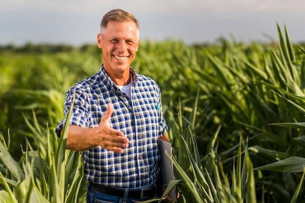 Homem sorridente, esticando a mão para a câmera Foto gratuita